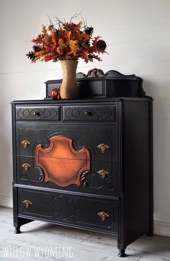 A black dresser with a gorgeous natural wood design on the front