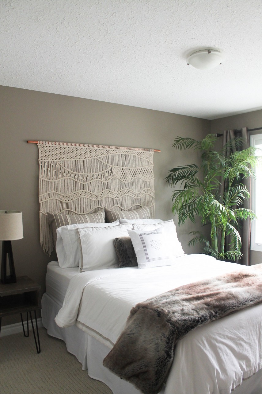 A macrame headboard on a copper pipe commands the room.