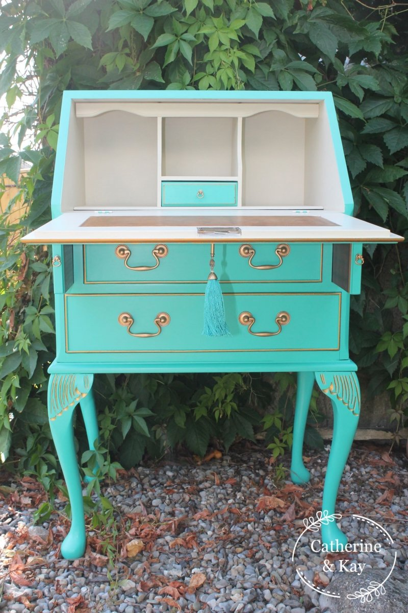 This secretary writing desk has gold hardware and a tassel