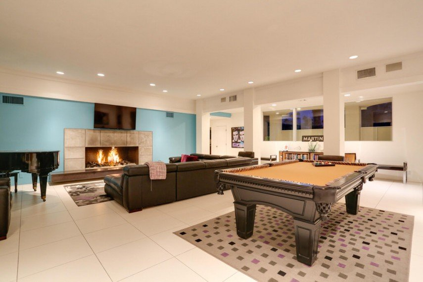 Sleek basement pool room with a fireplace and piano - grand design