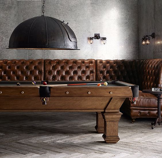 The iron lighting and tufted couch give a lot of elegance to the decor in this billiards room