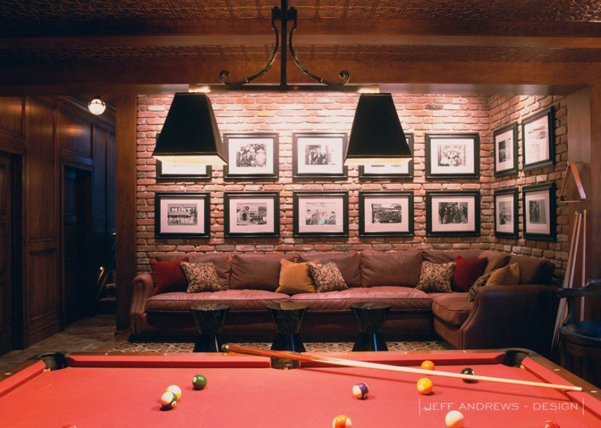 Framed photos on brick - and a comfortable couch - give this billiards room a jazz club feel.