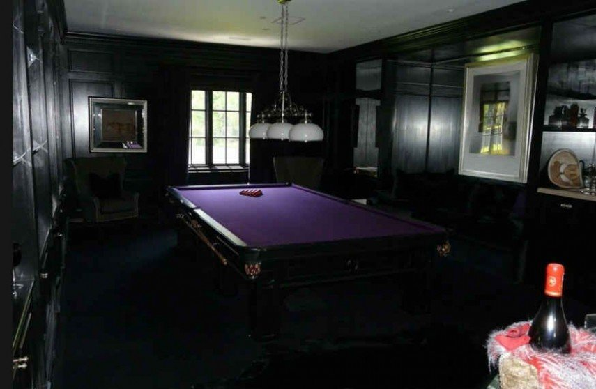 Wood walls and a dark wood billiards table with purple felt
