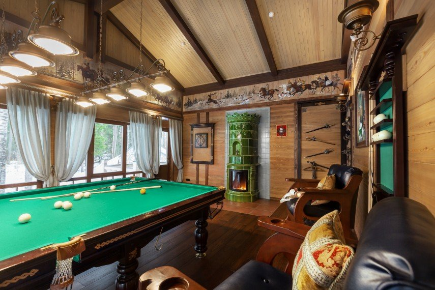 A beautiful tiled wood stove enhances the billiard room experience