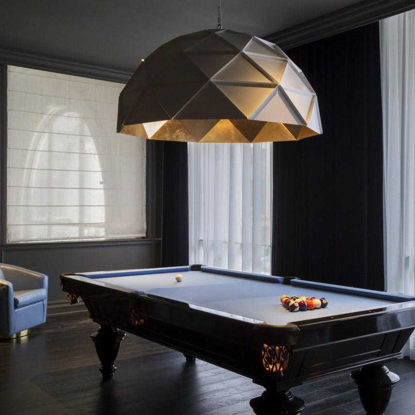 This hanging geometric dome lighting certainly sets the bar for the pool table room design