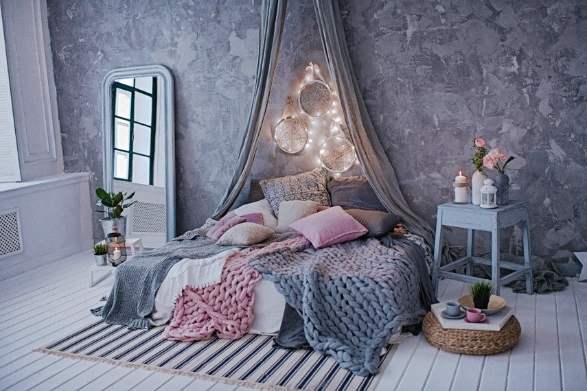 Gray and pink bedroom with a draping headboard and woven blankets