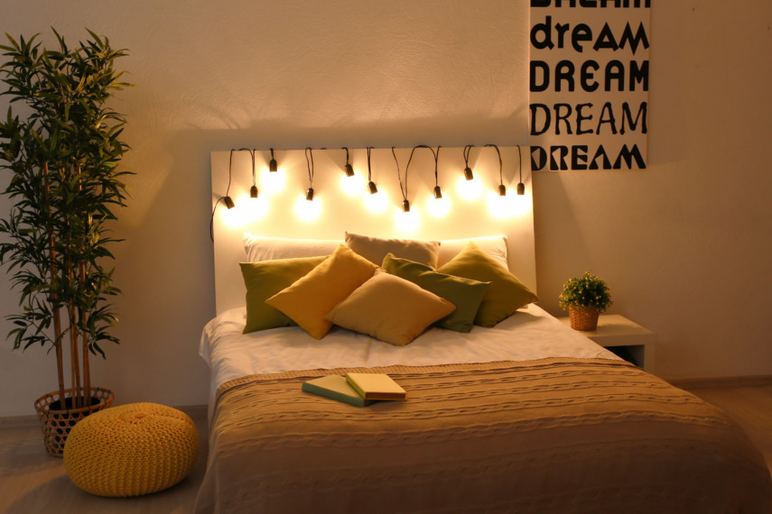 Bed with hanging lamps and a large plant