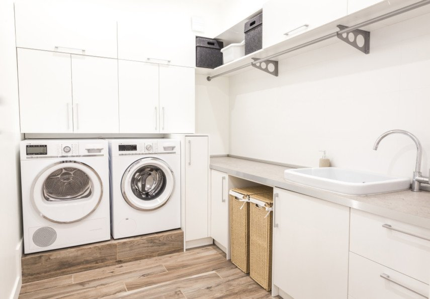 L-shaped layout laundry room with raised side-by-side washer and dryer