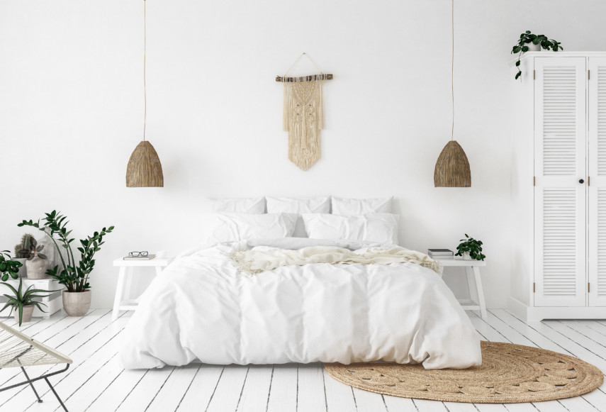 All white bedroom with white wooden floors and plants