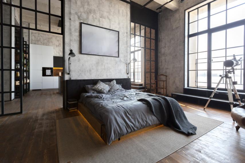 Modern bedroom with concrete walls, dark furniture and big windows