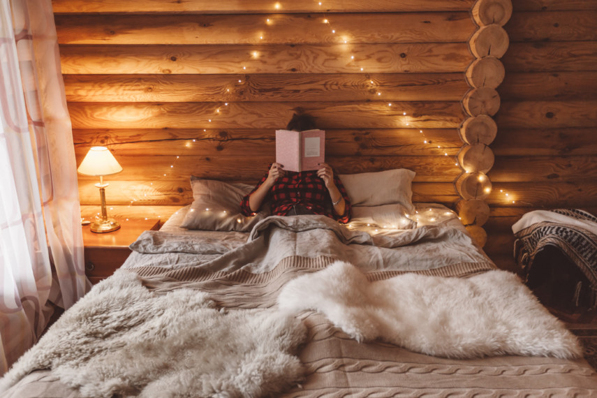 Woman reading in bed with fur throws, log walls, and string lights