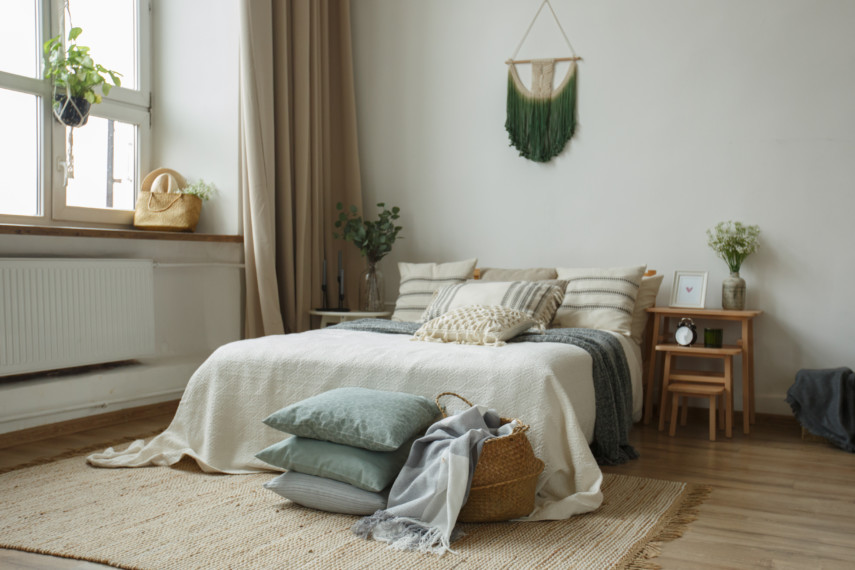 Soft toned bedroom with stacks of cushions