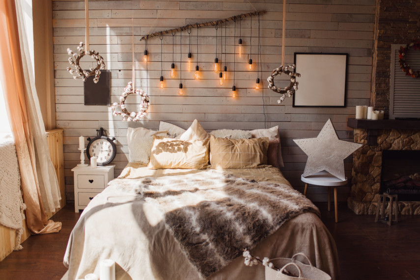 Eclectic neutral tone bedroom with candles, hanging lights, and a fireplace