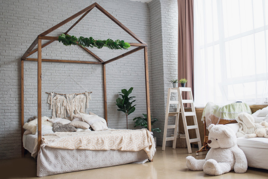 White brick wall bedroom with a tall wooden bed frame and a large plush teddy bear