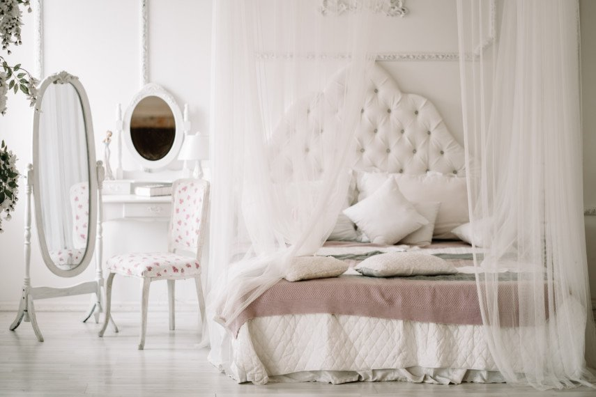 Airy bedroom decor with canopy bed, quilted headboard, and elegant accessories
