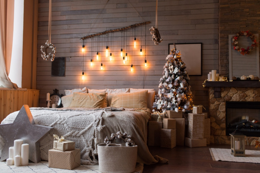 Bedroom filled with candles, a Christmas tree, and hanging lights