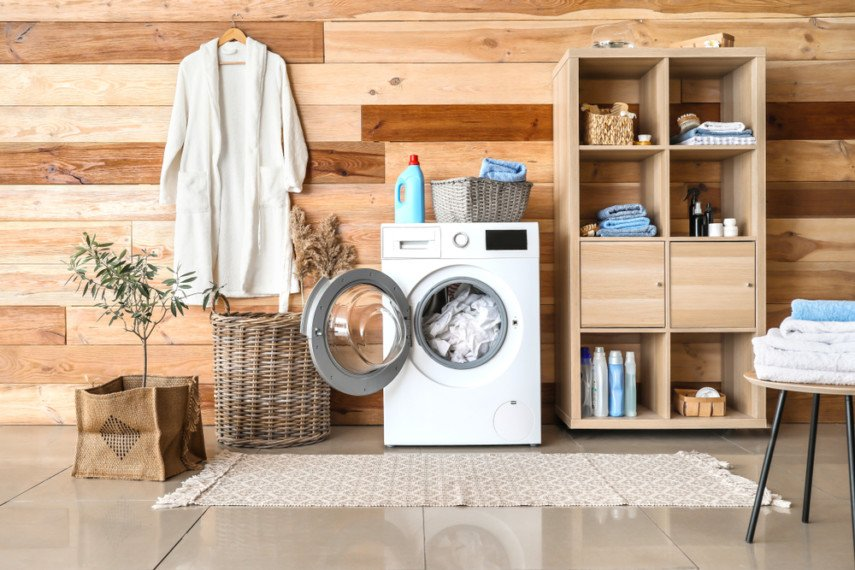 Wood wall paired with wood shelving creates a warm, inviting laundry room