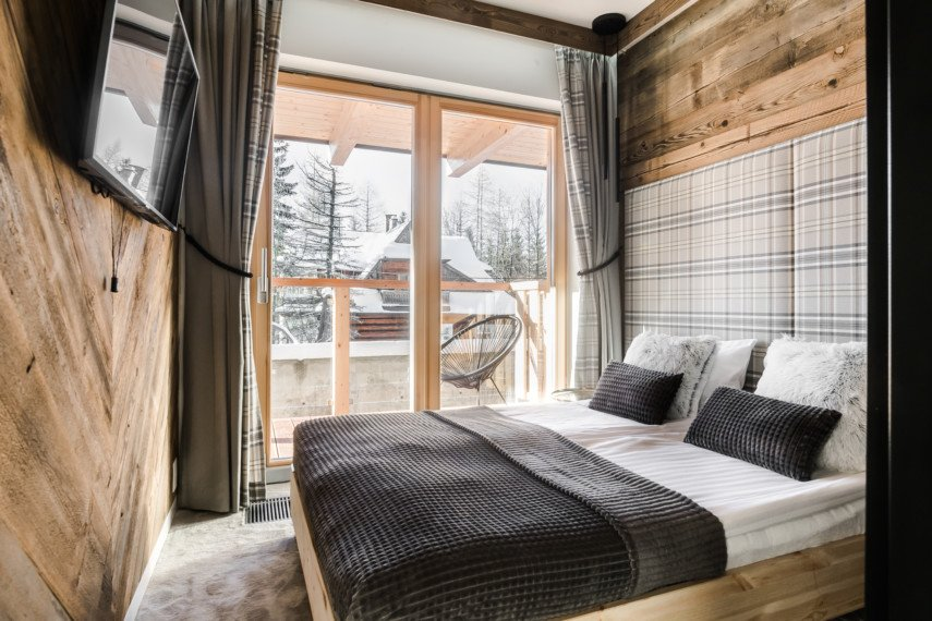 Small bedroom with wooden walls and a balcony