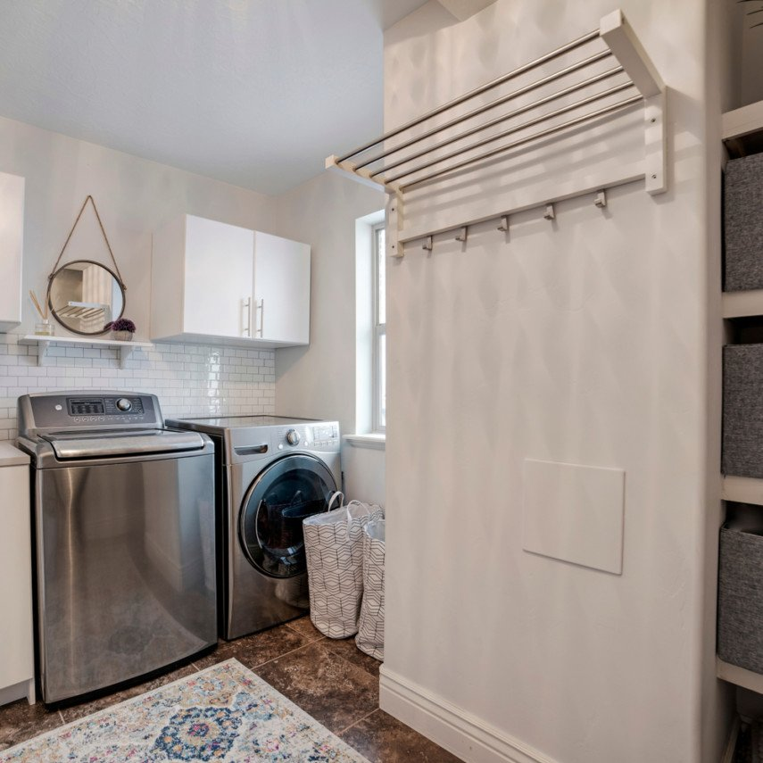 Short leg of L-shaped layout laundry idea has wall-mounted drying rack with hooks