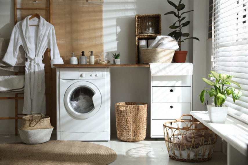 Single wall laundry room layout with white floor, utility sink and hanging bar