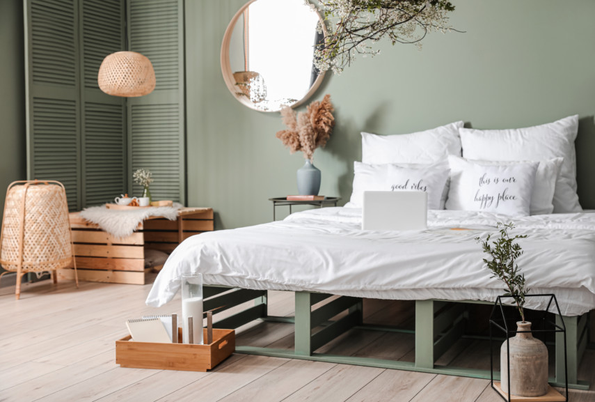 Bedroom with pastel walls, and a simple white bedspread