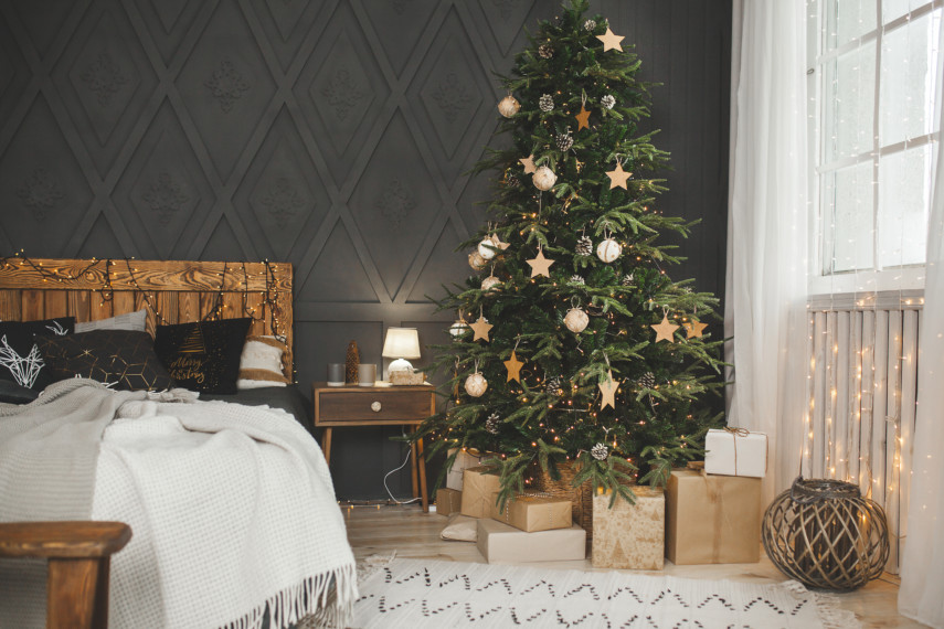 Bedroom with dark wallboards and a Christmas tree