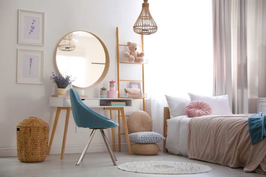 Light and airy bedroom with a desk, shelf, and round mirror
