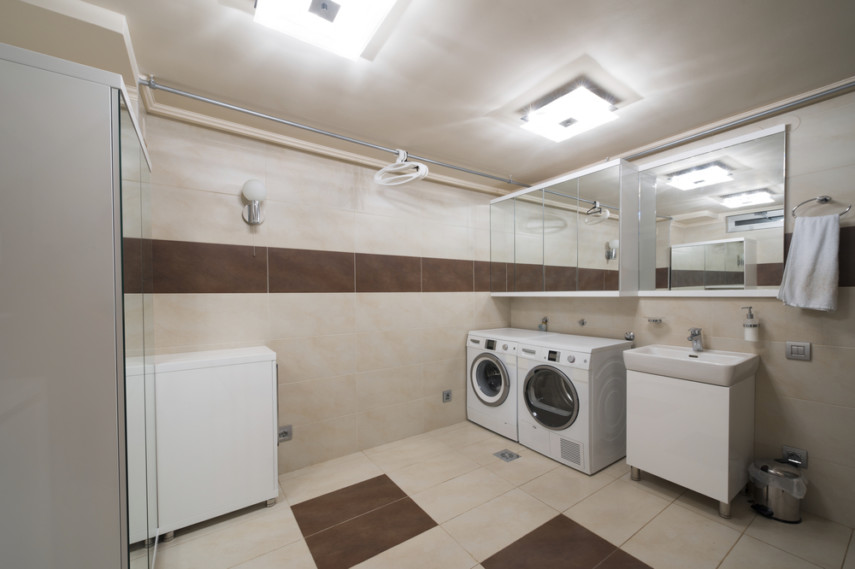 Large laundry room layout with hanging rod, side-by-side appliances and utility sink