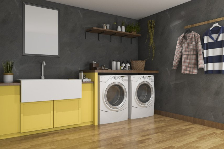 Bright cabinet of utility sink constrast with dark laundry room walls