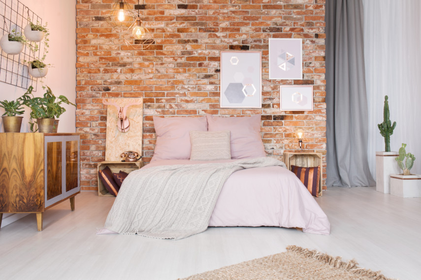 Bedroom with modern furniture and a brick wall