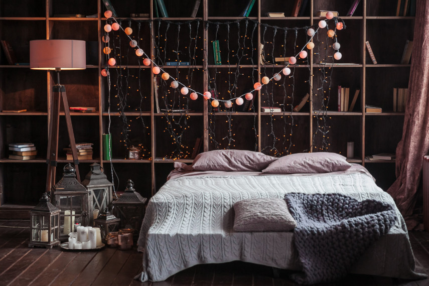 Bedroom with full wall bookshelves and festive lights