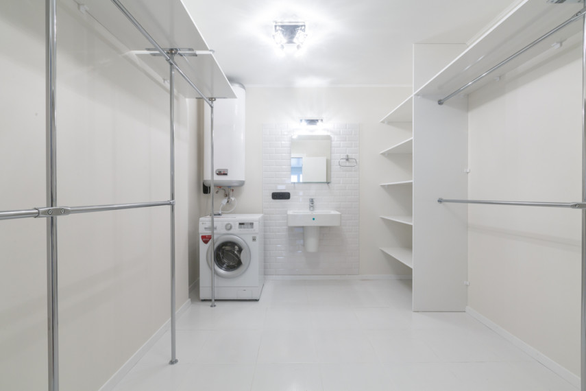 Large space laundry room layout idea with spacious shelving and multiple hanging bars