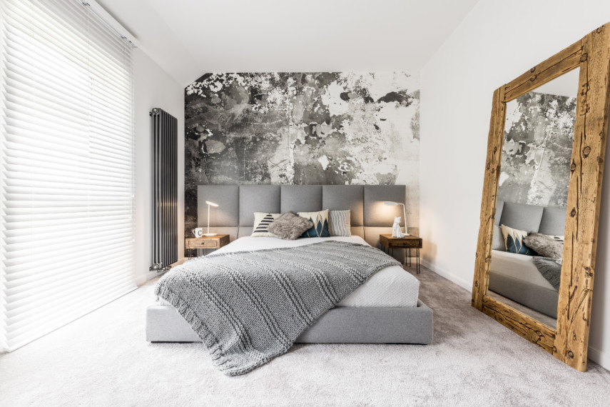 Gray and white bedroom with large floor to ceiling wooden mirror