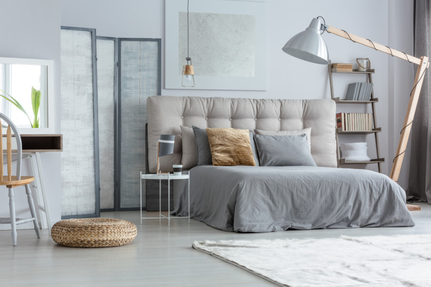 Gray bedroom with quilted headboard and large lamp