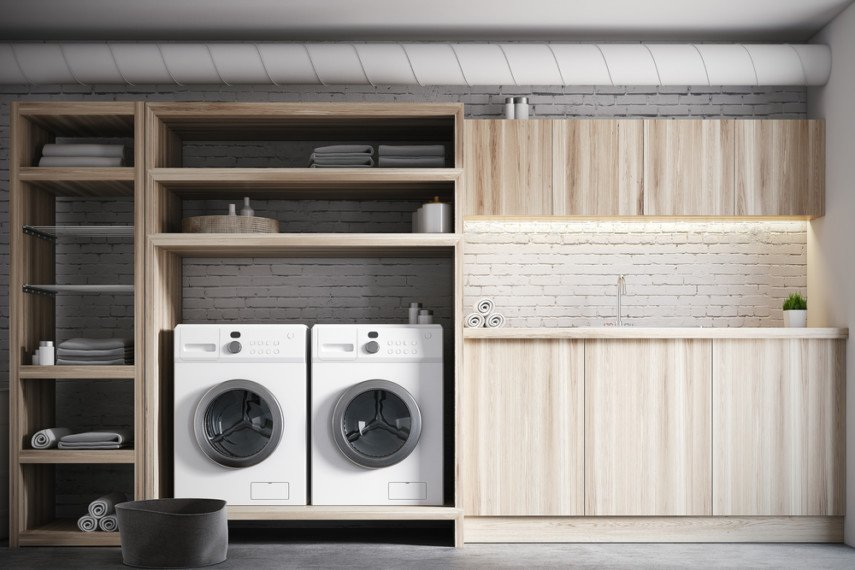 Utility sink, 2 washing machines, and open shelving on white brick wall