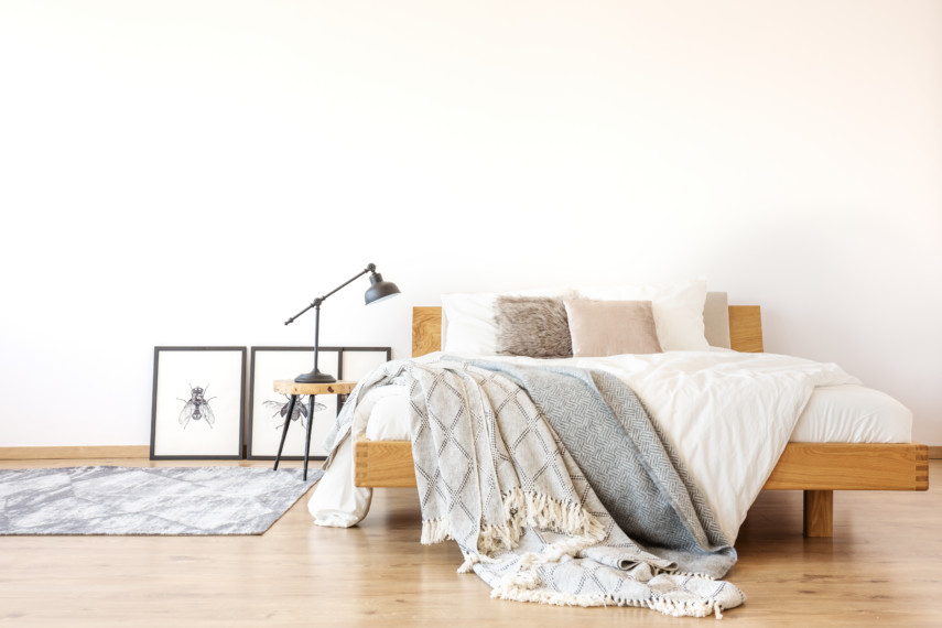 Minimal bedroom with wooden bed and neutral tones
