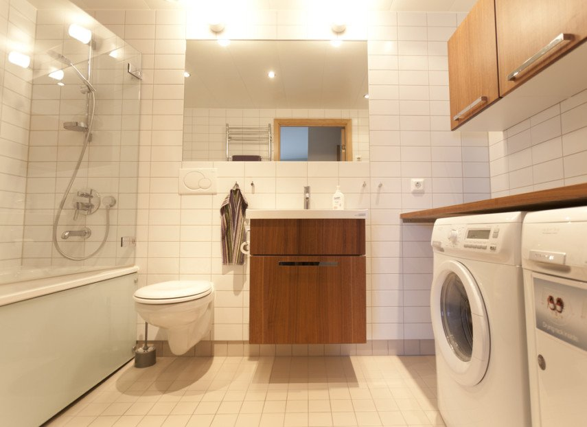 Modern style bathroom laundry combo contrasts wood cabinet utility sink with white appliances