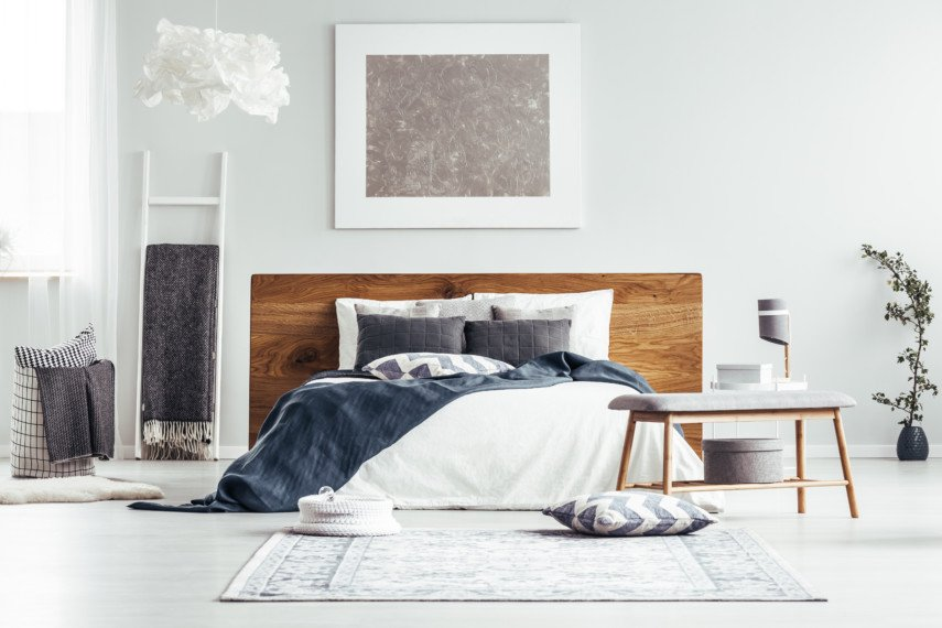 Bedroom with simple furniture and a standout wooden headboard