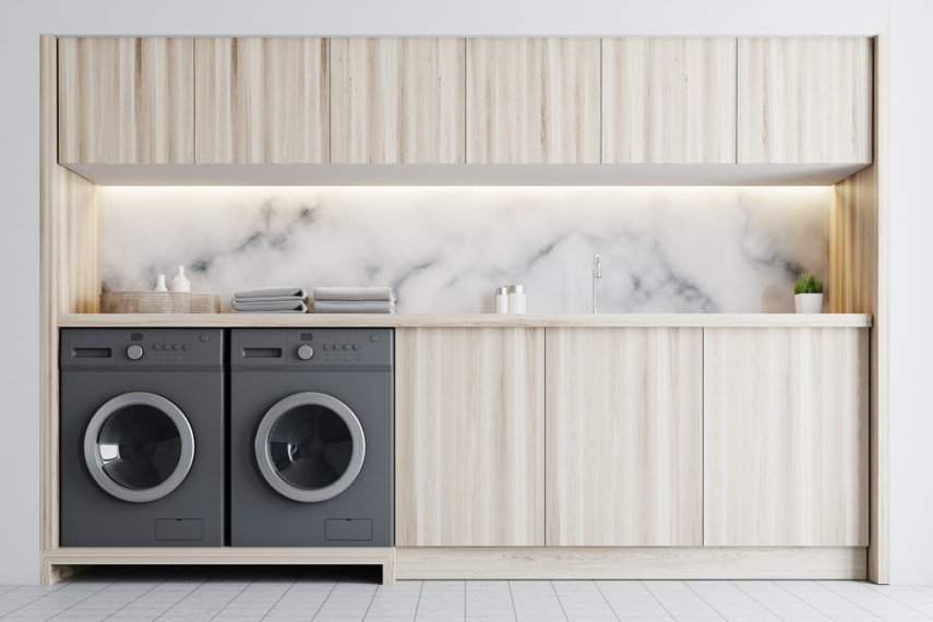 One wall laundry room ideas - marble backsplash, side-by-side machines, overhead caminets
