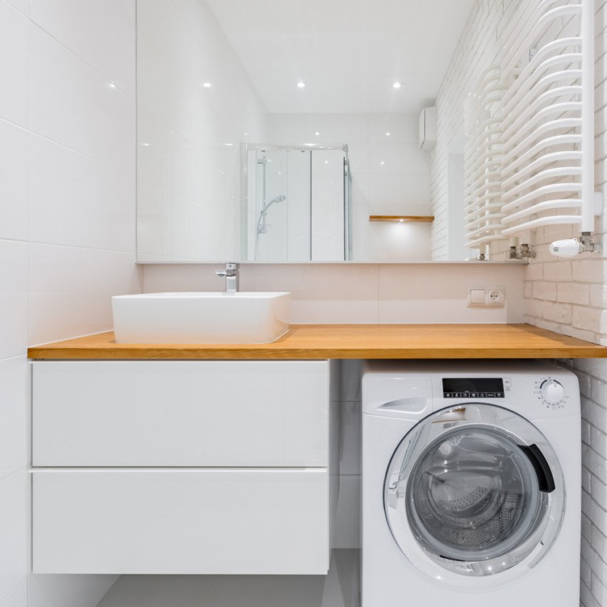 Create a practical bathroom laundry room combo layout at one end of the room